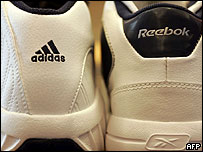 A pair of Adidas shoes and a pair of Reebok shoes