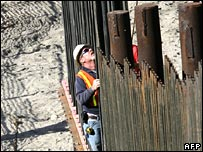 US construction worker builds new fence dividing the US-Mexican border