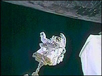 Astronaut Steve Robinson approaches the belly of Discovery