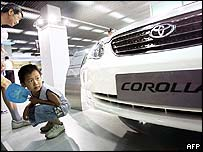 Young child looks at a Toyota Corolla