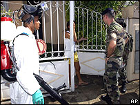 A soldier and city employees ask to enter a house with spray equipment in Saint Denis, the main city of Reunion