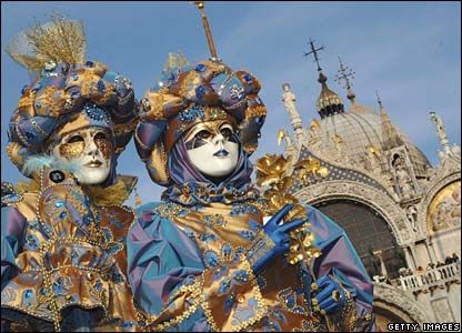 Dos venecianos en disfraces azul y dorado.