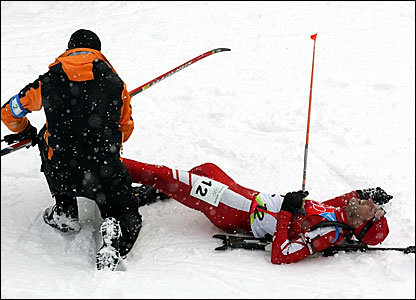 Poland's Tomasz Sikora is helped out of his skis after collapsing at the end of the race