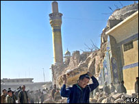 An Iraqi man helps clear the rubble at Samarra's bombed al-Askari shrine