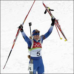 Anna Carin Olofsson celebrates winning gold in the women's inaugural 12.5km biathlon