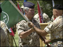 Incoming Italian commander, Mauro Del Vecchio (R), receives Isaf flag from General Gerhard Back