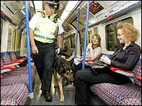 A British Transport Police officer and his dog patrol a Tube passing through reopened Russelll Square station