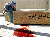 A man grieves over the coffin of a relative killed in Baquba