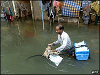 A milkman takes his bike through a waterlogged street in Mumbai on Tuesday