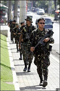 Soldiers patrol outside the offices of a Philippines television station