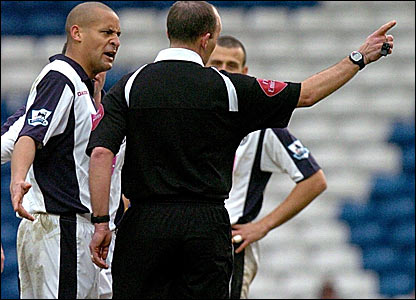 Referee Mike Dean shows West Brom's Nigel Quashie the way to the dressing room