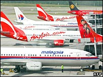 Aircraft from Malaysian Airlines and Malaysia's budget carrier Air Asia sit parked on the tarmac of Kuala Lumpur's International Airport