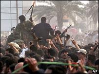 Shia militia members escort cleric Moqtada al-Sadr in Basra