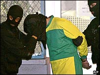 Rachid Ramda (in yellow and green) held by officers