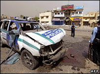 Police stand beside patrol car damaged in Baghdad blast