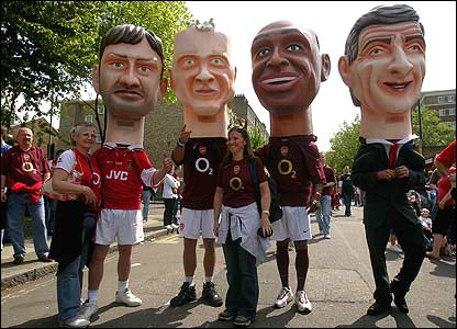 Fans wearing over-sized Tony Adams, Dennis Bergkamp, Thierry Henry and Arsene Wenger heads