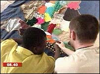 a teacher guides a Milton Margai pupil round a tactile map of the UK