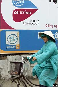 A woman cycling past an Intel sign in Ho Chi Minh City