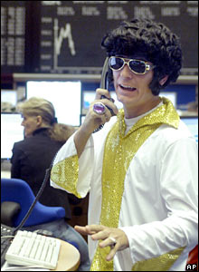 A stock trader wearing an Elvis costume talks on the phone in front of the German Stock Index