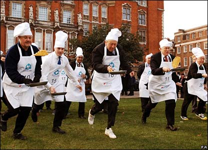 Teams compete in the annual parliamentary charity pancake race in London, UK
