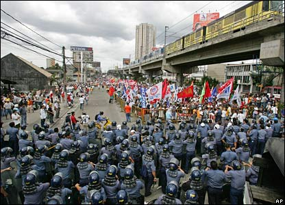 Riot police watch protesters calling for resignation of Philippine President Gloria Arroyo, in Manila