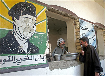 Iraqis living in an abandoned army barracks in Basra talk as they stand near a defaced mural of Saddam Hussein