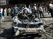 Locals look at the wreckage of a car used in one of the Baghdad blasts