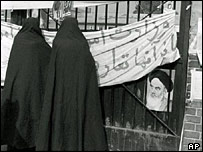 Women in chadors look in at the US Embassy in Tehran, 1979