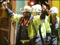 Todd Russell and Brant Webb wave as they emerge from the mine