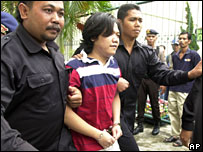 Police escort Anif Solchanudin to the trial in Denpasar