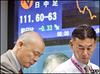 Japanese businessmen walk past sign showing the strength of the yen against the dollar