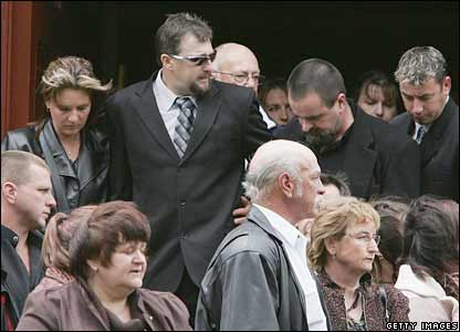 Mr Russell (in dark glasses) attends the funeral of Larry Knight