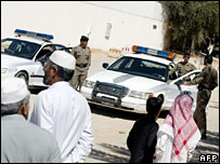 Saudi security forces stand guard on a road leading to the house where five men were killed during clashes in Riyadh