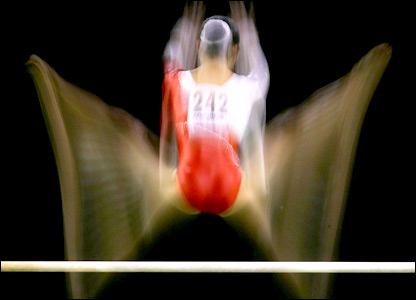 A gymnast performs on the uneven bars