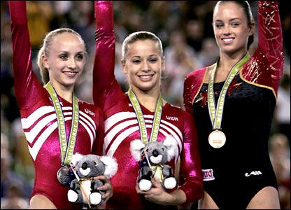 Three gymnasts celebrate their gymnastics medals