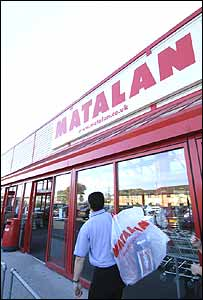 Man walking past a Matalan store