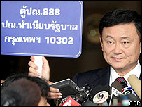 Thai Prime Minister Thaksin Shinawatra shows a placard bearing the postal address of Government House and urged Thais to mail him messages of support, in Bangkok, 01 March 2006.