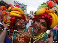 Two men wearing headdresses made of tropical fruits
