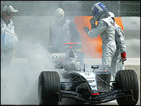 David Coulthard stands next to his stricken McLaren in Bahrain in 2004