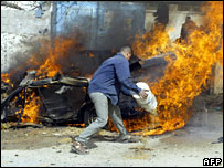 A Palestinian man tries to extinguish a burning vehicle struck during an Israeli air strike