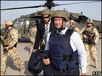 Australian Deputy Prime Minister and Trade Minister Mark Vaile (C), flanked by members of the Australian military, prepares to leave Iraq after meeting with the Iraqi leaders in Baghdad