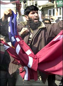 A Kashmiri protester burns US and Danish flags