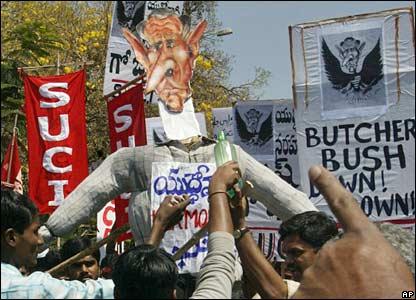 Miembros de partidos de izquierda colocan kerosén en un muñeco del presidente Bush