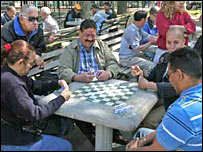 Men and women playing dominoes in J Wood Wright park in the Washington Heights