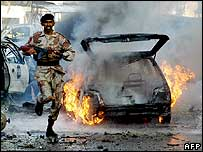 A Pakistani paramilitary soldier runs in front of a burning vehicle after a bomb blast outside a hotel in Karachi