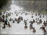 People cool off in a canal in Lahore, Pakistan, on 8 May 2006