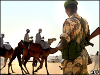 AU soldier in Darfur looks at people passing on camels