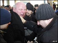 Alexander Kozulin (left) clashes with police in Minsk