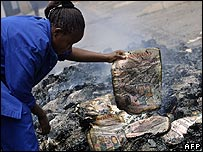 A woman holds the charred remains of a copy of The Standard