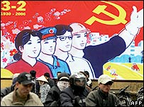Motorcyclists ride past a poster marking the 76th anniversary of the foundation of the ruling Vietnam Communist Party, 25 January 2006 in downtown Hanoi.